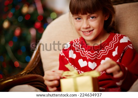 Portrait of cute girl with giftbox looking at camera - stock photo