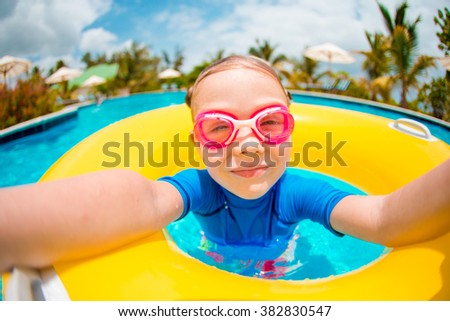 Portrait of cute girl with inflatable rubber ring having fun in swimming pool - stock photo