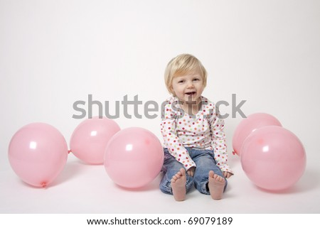 Portrait of cute girl with pink balloons having fun at the party - stock photo