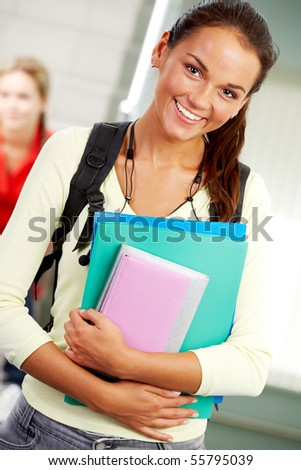 Portrait of cute girl with textbook in hands looking at camera in college - stock photo
