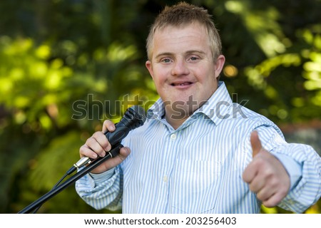 Portrait of cute Handicapped boy with microphone doing thumbs up. - stock photo