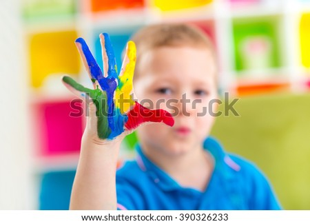 Portrait of cute happy boy with colorful painted hands - stock photo