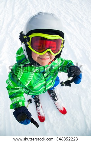 Portrait of Cute happy skier boy in a winter ski resort. - stock photo