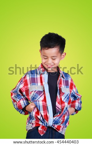 Portrait of cute happy young Asian boy over green background - stock photo