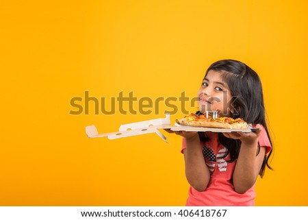portrait of cute indian girl holding an open box of pizza, excited asian girl opening pizza box  showing smile on face, standing over yellow background - stock photo