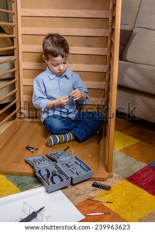 Portrait of cute kid assembling with tools a new furniture for home. Family leisure concept - stock photo
