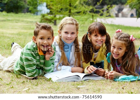 Portrait of cute kids lying on lawn and looking at camera with open book near by - stock photo