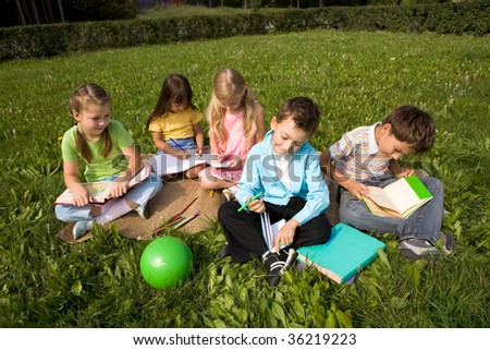 Portrait of cute kids reading books and drawing in park together - stock photo