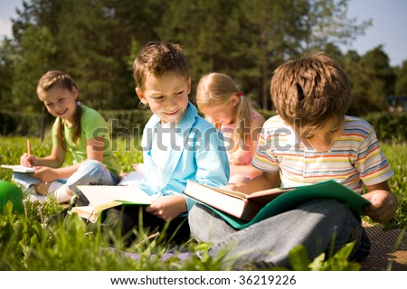 Portrait of cute kids reading books in natural environment together - stock photo