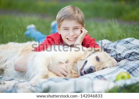 Portrait of cute lad and his fluffy pet lying on plaid - stock photo