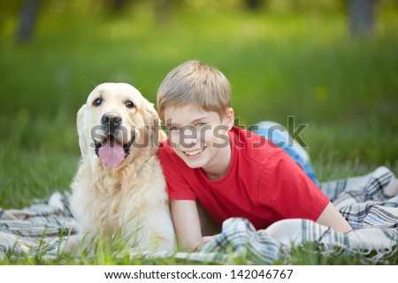 Portrait of cute lad and his friendly pet lying on plaid - stock photo