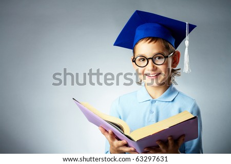 Portrait of cute lad in eyeglasses and student hat holding open book - stock photo