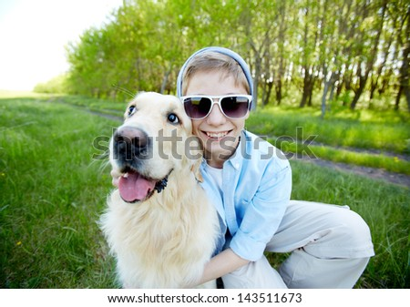 Portrait of cute lad in sunglasses and his fluffy friend outdoors - stock photo