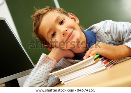 Portrait of cute lad with copybooks looking at camera in classroom - stock photo