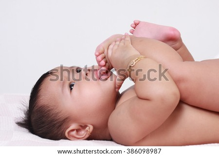 Portrait of cute little Asian baby girl lying down on bed and sucking her toes - stock photo