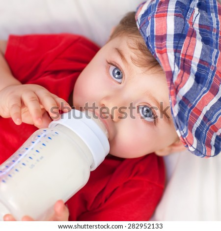 Portrait of cute little baby boy drinking milk, lying down on the bed and eating, baby food formula, healthy nutrition for kids - stock photo