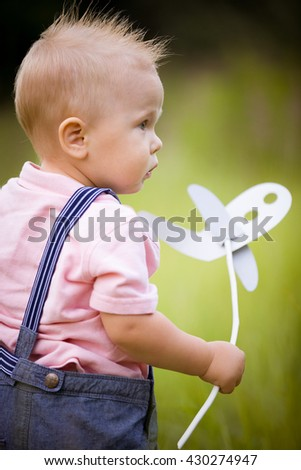 Portrait of cute little blond toddler boy holding paper plane toy on a stick and looking into distance. Adorable child walking in park on sunny day. Summertime Outdoors. Childhood, lifestyle concept - stock photo