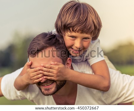 Portrait of cute little boy and his handsome young dad looking camera and smiling while resting in the park. Son is sitting pickaback and covering his father eyes - stock photo