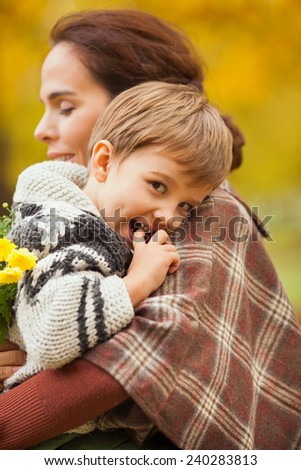 Portrait of cute little boy in his mother's arms - stock photo