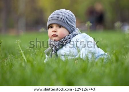 Portrait of cute little boy in park in spring - stock photo