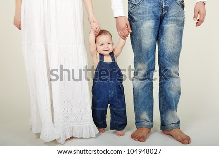 Portrait of cute little boy stand with mother and father help - stock photo