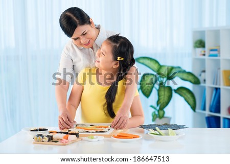 Portrait of cute little girl and her grandmother cooking sushi together - stock photo