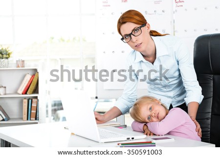 Portrait of cute little girl and her mother while working day. Business woman trying to amuse her daughter. Girl is bored - stock photo