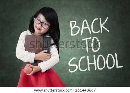 Portrait of cute little girl back to school and standing in the class while holding a book - stock photo