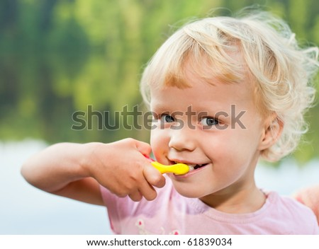 Portrait of cute little girl  brushing teeth  outdoors - stock photo
