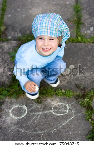 Portrait of cute little girl drawing a car on the ground - stock photo