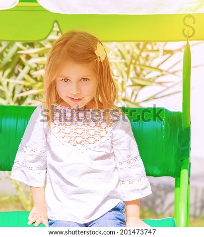 Portrait of cute little girl having fun on swing on play garden, preschooler spending summer holidays in the camp, carefree childhood concept - stock photo