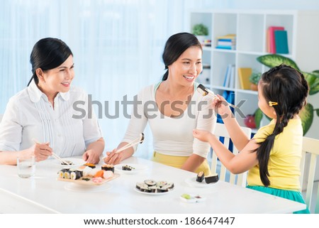 Portrait of cute little girl, her mother and grandmother eating sushi in the kitchen - stock photo