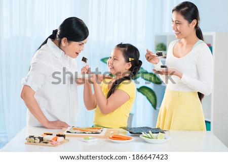 Portrait of cute little girl, her mother and grandmother tasting sushi in the kitchen - stock photo