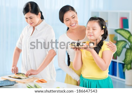 Portrait of cute little girl holding tray with sushi in the kitchen with her mother and grandmother near by - stock photo