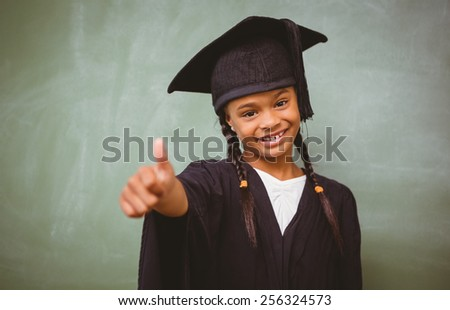 Portrait of cute little girl in graduation robe gesturing thumbs up - stock photo