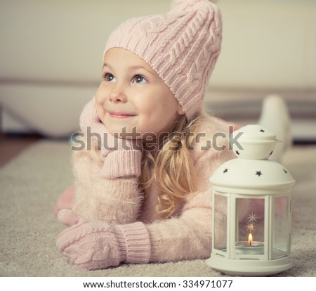 Portrait of cute little girl in hat and gloves at Christmas time - stock photo