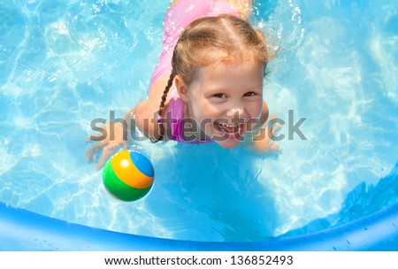 Portrait of cute little girl in swimming pool outdoors - stock photo