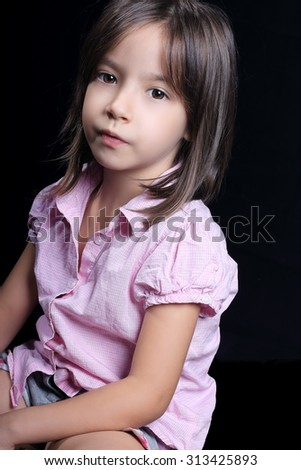 Portrait of cute little girl looking at camera, on dark background - stock photo