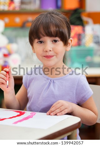 Portrait of cute little girl painting in art class - stock photo