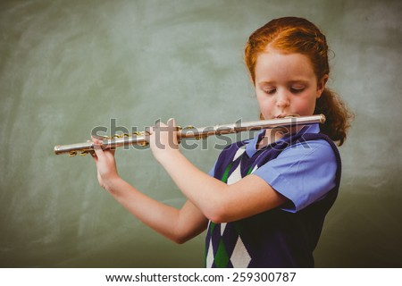 Portrait of cute little girl playing flute in classroom - stock photo