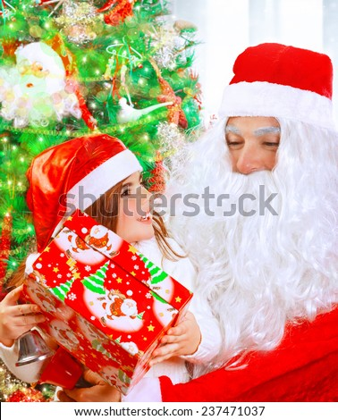 Portrait of cute little girl receives present from Santa Claus, sitting near decorated Christmas tree with beautiful wrapped gift box, happy winter holidays concept - stock photo