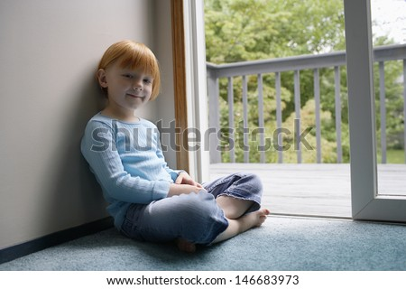 Portrait of cute little girl sitting by balcony at home - stock photo