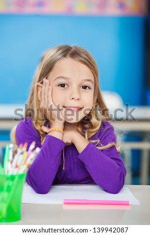 Portrait of cute little girl sitting with hand on chin at desk in kindergarten - stock photo