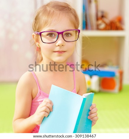 Portrait of cute little girl wearing glasses, spending time in daycare with book in hands and preparing to go to elementary school, start of education season  - stock photo