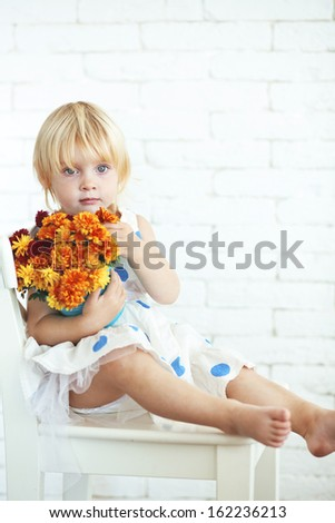 Portrait of cute little girl with bouquet of flowers - stock photo