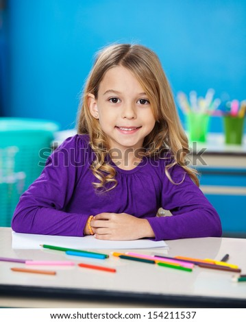 Portrait of cute little girl with colored sketch pens and paper in kindergarten - stock photo