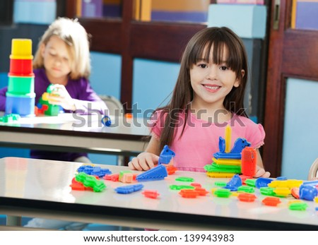 Portrait of cute little girl with construction block while friend playing in background at preschool - stock photo
