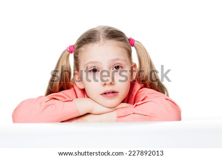 Portrait of cute little girl with head on hands sitting at table isolated over plain background - stock photo
