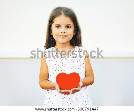 Portrait of cute little girl with red paper heart over white - stock photo