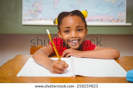 Portrait of cute little girl writing book in classroom - stock photo